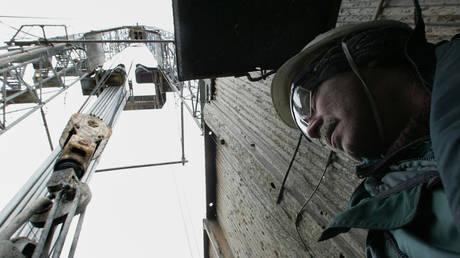A Rosneft worker stands beneath a crane at the Yuganskneftegaz oil production station near the Siberian town of Nefteyugansk, Russia © Reuters / Sergei Karpukhin