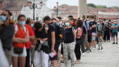 """People queue to enter San Marco Dome, as the region of Veneto becomes a """"white zone"""", following a relaxation of coronavirus disease (COVID-19) restrictions with only masks and social distancing required, in Venice, Italy, June 7, 2021. © REUTERS/Yara Nardi"""
