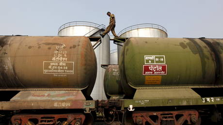 A worker walks atop a tanker wagon to check the freight level at an oil terminal on the outskirts of Kolkata, India