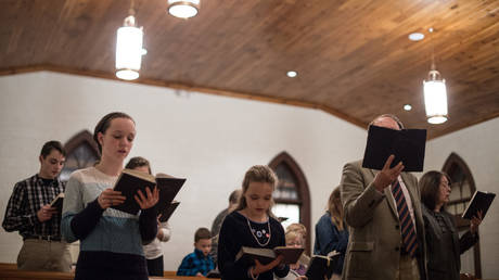 FILE PHOTO: People sing hymns at Grace Orthodox Presbyterian Church during a Sunday evening service in Lynchburg, Virginia. © Nicholas Kamm / AFP