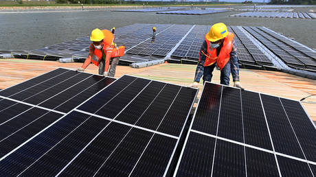 This photograph taken on February 3, 2021 shows workers assembling solar panels on the shore of Tengeh reservoir as part of efforts to construct a floating solar power farm in Singapore. © Roslan RAHMAN / AFP