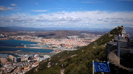 A general view shows the Spanish city of La Linea de la Concepcion and the tarmac of the Gibraltar International Airport while tourists stand on the top of the Rock next to the European Union flag, in the British overseas territory of Gibraltar, September 14, 2016.