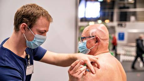 FILE PHOTO: A medical worker vaccinates a man against the coronavirus disease (COVID-19) in Frederikshavn, Jutland, Denmark, April 12, 2021. © Henning Bagger/ Ritzau Scanpix/via REUTERS
