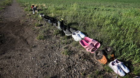 Shoes are seen on a path leading to the former Brandon Indian Residential School where researchers, partnered with the Sioux Valley Dakota Nation, located 104 potential graves in Brandon, Manitoba, Canada, June 12, 2021. © REUTERS/Shannon VanRaes