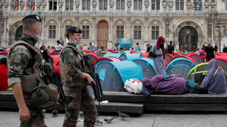 French soldiers walk past tents installed by migrants in front of the City Hall in Paris. © Reuters / Gonzalo Fuentes