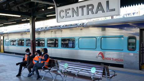 Transport workers sit together on an empty train platform in Sydney, Australia, June 26, 2021.