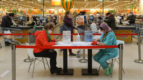 """A woman fills in a form before receiving a dose of with Russian Gam-COVID-VAK (trademark """"Sputnik V"""") coronavirus vaccine at a vaccination point at a Globus hypermarket, in Moscow, Russia."""