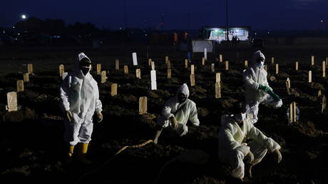 Gravediggers take a break as they work at the burial area provided for coronavirus victims, in Jakarta, Indonesia on June 28, 2021.