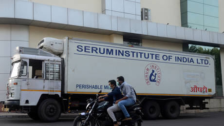 Men ride on a motorbike past a supply truck of India's Serum Institute, the world's largest maker of vaccines, which is working on a vaccine against the coronavirus disease (Covid-19) in Pune, India, (FILE PHOTO) © REUTERS/Euan Rocha