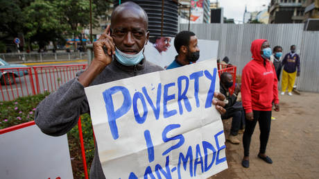 """FILE PHOTO. A protester holds a message """"Poverty is man-made"""" as they demand the Kenyan government take action for better living conditions in the Covid-19 pandemic during a May Day rally marking the international labor day in Nairobi on May 1, 2021, KENYA. © AFP / Ed Ram"""