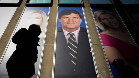 FILE PHOTO: People pass by a promo of Fox News host Tucker Carlson on the News Corporation building in New York