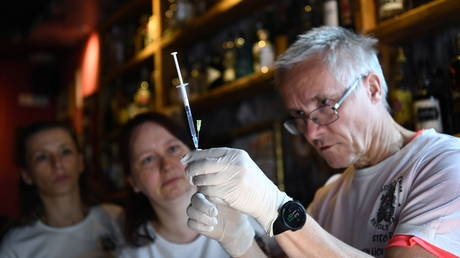 Pediatrician Dr. Steffen Lueder prepares a Johnson & Johnson COVID-19 vaccine injection before starting vaccination at the Revolte Bar, which has been able to reopen after coronavirus disease (COVID-19) restrictions were eased, in Berlin, Germany June 13, 2021. © Reuters / Annegret Hilse