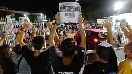 Apple Daily journalists hold freshly-printed copies of the newspaper's last edition while acknowledging supporters gathered outside their office in Hong Kong early on June 24, 2021. © AFP / Daniel SUEN