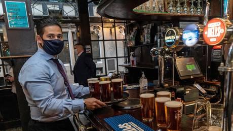 FILE PHOTO: A bartender in a pub in London, UK, May 2021. © Niklas Halle'n/AFP