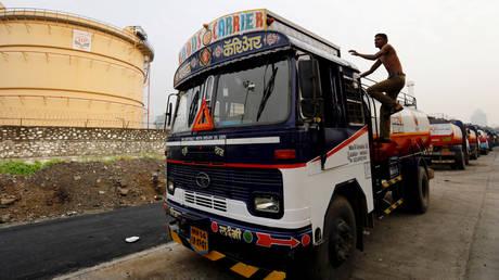 A man climbs an an oil tanker parked outside a fuel depot in Mumbai, India
