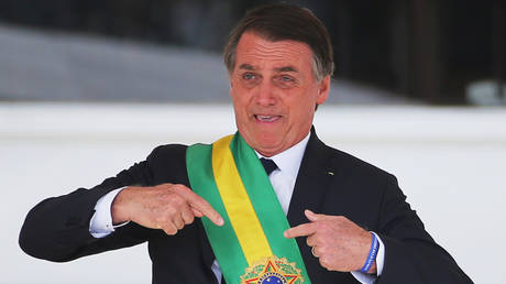 President Jair Bolsonaro gestures after receiving the presidential sash from outgoing President Michel Temer. ©REUTERS / Sergio Moraes