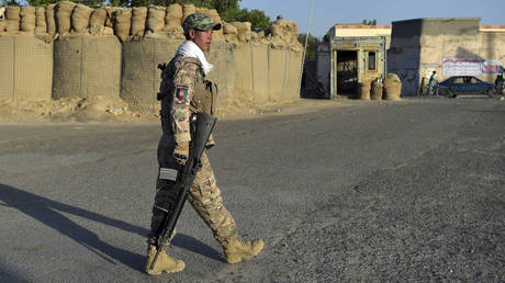 In this photo taken on June 3, 2021, a policeman walks outside his outpost along a roadside in Ghazni, Afghanistan.