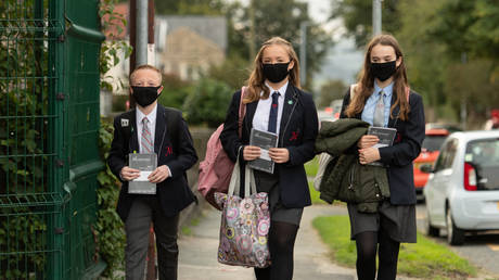 Pupils wearing facemasks as a precaution against the transmission of the novel coronavirus arrive to attend Moor End Academy in Huddersfield, northern England on September 11, 2020. © OLI SCARFF / AFP