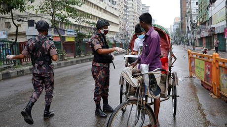 Members of Border Guard Bangladesh (BGB) check commuters at a checkpost during a countrywide lockdown in Dhaka, Bangladesh, July 1, 2021. © REUTERS/Mohammad Ponir Hossain