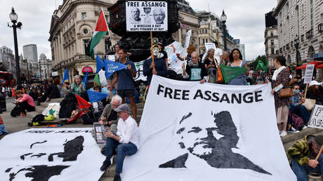 People protest for Julian Assange at Piccadilly Circus on his 50th birthday.