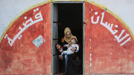 Palestinian families, fleeing from their homes with their belongings, take shelter in a school owned by the United Nations Relief and Works Agency for Palestine Refugees in the Near East. © Ali Jadallah/Anadolu Agency via Getty Images
