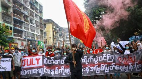 Protesters hold banners as they take part in a demonstration against the military coup and to mark the anniversary of 1962 student protests against the country's first junta in Yangon on July 07, 2021. © Stringer/Anadolu Agency via Getty Images