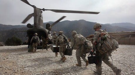 US soldiers board an Army Chinook transport helicopter after it brought fresh soldiers and supplies to the Korengal Outpost on October 27, 2008 in the Korengal Valley, Afghanistan. © John Moore/Getty Images