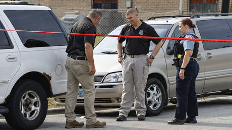 Law enforcement officers investigate a crime scene near the border between the Morgan Park and West Pullman neighborhoods on July 7, 2021 in Chicago, Illinois. © Kamil Krzaczynski/Getty Images