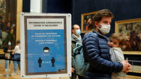 Visitors wearing protective face masks walk past a sign with health and safety measures for visitors at the Louvre museum in Paris, May 19, 2021. © REUTERS/Sarah Meyssonnier