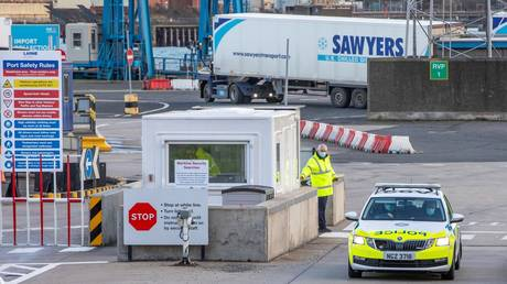 FILE PHOTO. Police and officials patrol as truckers carrying freight from Scotland disembark a ferry at the Port of Larne in County Antrim, Northern Ireland. © AFP /  PAUL FAITH