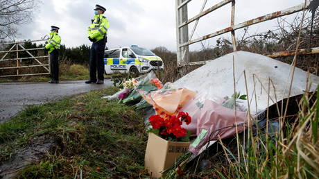 FILE PHOTO. Police officers stand near flowers for Sarah Everard, in Ashford, Britain