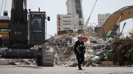 A rescue worker walks away from the remains of the collapsed 12-story Champlain Towers South condo building on July 08, 2021 in Surfside, Florida