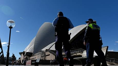 Police officers patrol the area outside the Sydney Opera House in Australia, June 2021. © Saeed Khan/AFP
