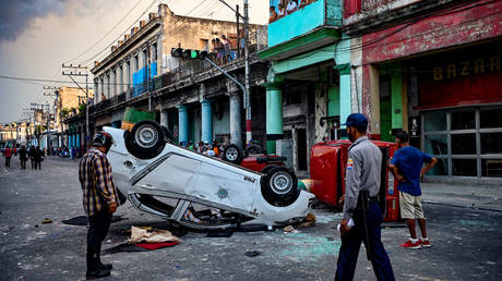 Police cars are seen overturned in the street amid demonstrations against Cuban President Miguel Diaz-Canel in Havana, on July 11, 2021