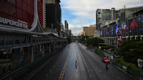 A man crosses the road on Ratchaprasong intersection in Bangkok on July 12, 2021, on the first day of stricter lockdown restrictions to try to contain the spread of the Covid-19 coronavirus. © AFP / Lillian SUWANRUMPHA