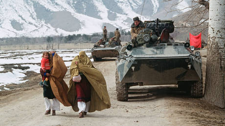 FILE PHOTO. Afghan women with children in their arms hurrying past Soviet armored vehicles along a serpentine highway outside Jalalabad, Afghanistan. © Sputnik