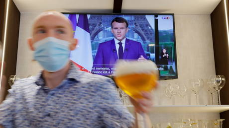A waiter serves beer in a pub as French President Macron, on TV, addresses the nation about the state of the coronavirus disease outbreak, in Cambrai, France, July 12, 2021 © Reuters / Pascal Rossignol
