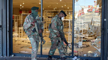 Members of the military keep guard outside a looted store as the country deploys army to quell unrest linked to jailing of former President Jacob Zuma, in Soweto, South Africa, July 13, 2021 © REUTERS/Siphiwe Sibeko