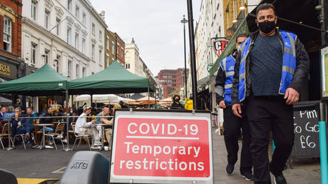 Covid-19 marshals walk past a Covid-19 road sign in Old Compton Street, Soho. © Vuk Valcic/SOPA Images/LightRocket via Getty Images
