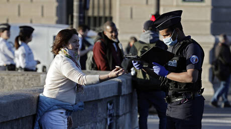A police officer checks a woman's self-certified note for being out before a two minute commemoration near the Notre-Dame Cathedral in Paris at 8 o'clock, on April 15, 2020. © THOMAS COEX / AFP