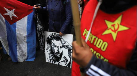 Demonstrators supporting the Cuban government display communist symbols, including an image of late Cuban President Fidel Castro, outside the Cuban embassy in Buenos Aires, Argentina, July 14, 2021.