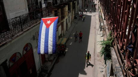 A Cuban flag hangs over a street in downtown Havana, Cuba, July 15, 2021.