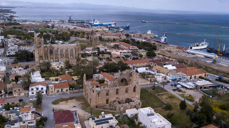 A pictured shows the Greek Church of Saint George (R) and the Saint Nicholas' Cathedral (L) (Lala Mustafa Mosque) in Famagusta, in the eastern coast of the self-proclaimed Turkish Republic of Northern Cyprus (TRNC), on April 9, 2021. © Birol BEBEK / AFP