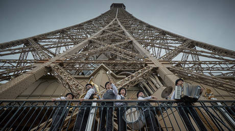 A brass band admires the view of Paris as the Eiffel Tower reopened for the first time in over 8 months on July 16, 2021 in Paris, France. © Kiran Ridley/Getty Images