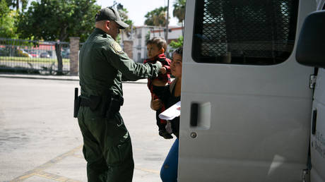 FILE PHOTO: A US Border Patrol agent assists a migrant woman and child as they're released from federal detention at a bus depot in McAllen, Texas, July 31, 2019.
