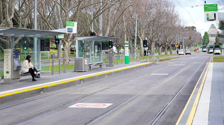 FILE PHOTO. A lone passenger sits at a tram stop in Melbourne, Australia on July 16, 2021.