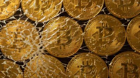FILE PHOTO: Representations of virtual currency bitcoin are seen through broken glass.