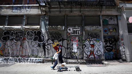 A man walks past graffiti on boarded up and closed storefronts in New York