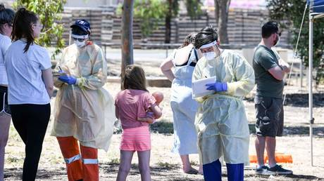 FILE PHOTO. Medical staff talk to people at a walk in station at Parafield Airport in Adelaide during day one of total lockdown across the state to fight Covid-19 coronavirus. © AFP / Brenton EDWARDS