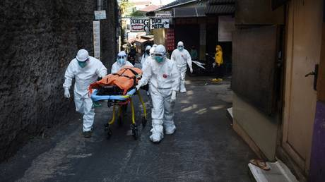 Health workers removed the body of a Covid-19 victim who died while isolating at home in Bandung on July 18, 2021, as skyrocketing Covid-19 infections and deaths are overwhelming hospitals. © AFP / Timur Matahari